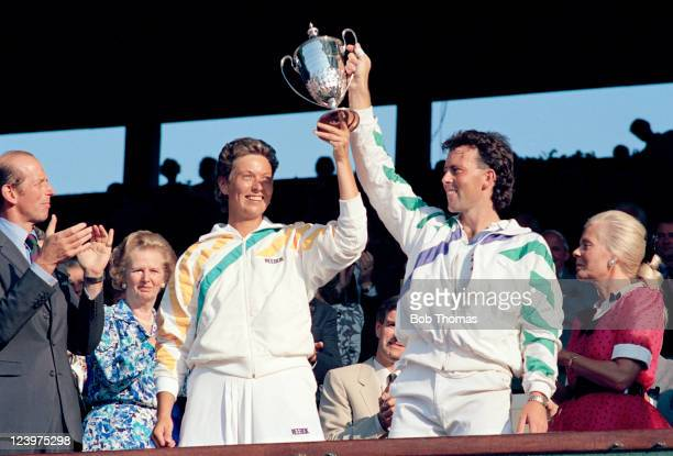 Jo Durie and Jeremy Bates of Great Britain hold the trophy aloft after winning the Mixed Doubles Final during the Wimbledon Lawn Tennis Championships...