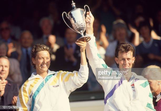 Jo Durie and Jeremy Bates of Great Britain lift the trophy after defeating Darren Cahill and Nicole Provis both of Australia in the Mixed Doubles...