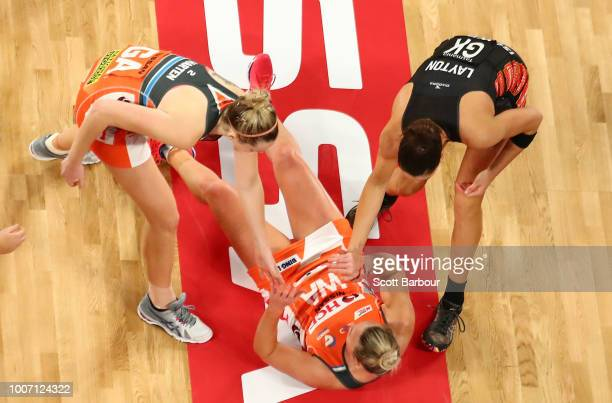 Jo Harten of the Giants and Sharni Layton of the Magpies help Kim Green of the Giants to her feet during the round 13 Super Rugby match between the...