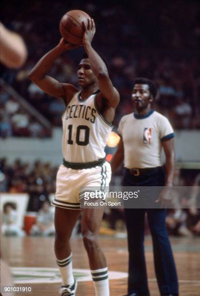 Jo Jo White and Dave Cowens of the Boston Celtics looks to pass the ball against the Washington Bullets during an NBA basketball game circa 1975 at...