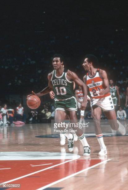 Jo Jo White of the Boston Celtics dribbles the ball past Dave Bing of the Washington Bullets during an NBA basketball game circa 1975 at the Capital...