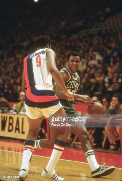 Jo Jo White of the Boston Celtics looks to drive on Dave Stallworth of the Baltimore Bullets during an NBA basketball game circa 1972 at the...