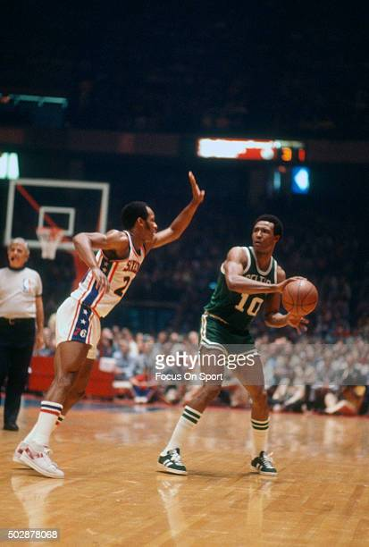 Jo Jo White of the Boston Celtics looks to pass the ball by Lloyd Free of the Philadelphia 76ers during an NBA basketball game circa 1975 at The...
