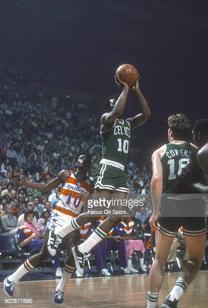 Jo Jo White of the Boston Celtics shoots in front of Kevin Porter of the Washington Bullets during an NBA basketball game circa 1975 at the Capital...