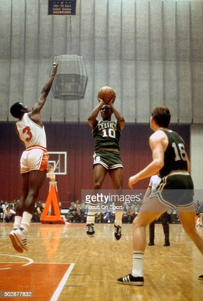 Jo Jo White of the Boston Celtics shoots over Fred Carter of the Baltimore Bullets during an NBA basketball game circa 1970 at the Baltimore Civic...