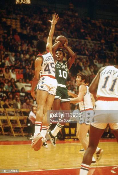 Jo Jo White of the Boston Celtics shoots over Phil Chenier of the Washington Bullets during an NBA basketball game circa 1975 at the Capital Centre...