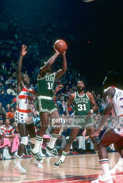 Jo Jo White of the Boston Celtics shoots the ball in front of Jimmy Jones of the Washington Bullets during an NBA basketball game circa 1976 at the...