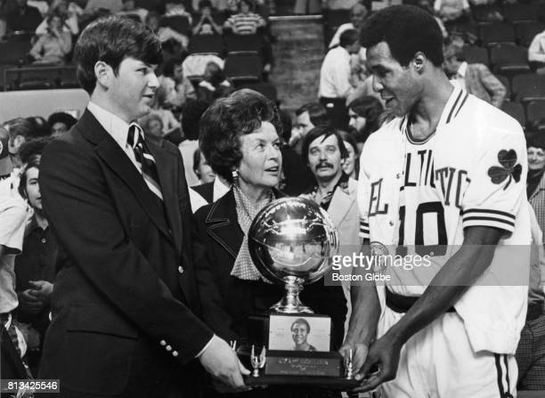 Jo Jo White right winner of the first annual Jack Barry Sportsmanship Award accepts his trophy from David and Mrs Nancy Barry son and wife of the...