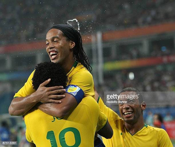 Jo of Brazil is celebrated by Ronaldinho and Marcelo after scoring the third goal during the Bronze Medal Match between Brazil and Belgium at...