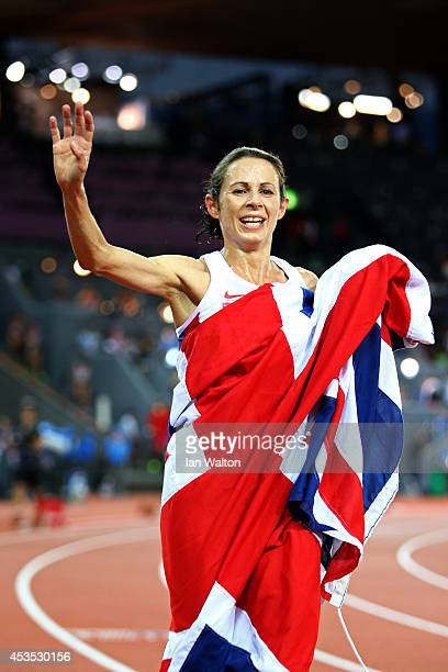 Jo Pavey of Great Britain and Northern Ireland celebrates with a Union Jack after winning gold in the Women's 10000 metres final during day one of...