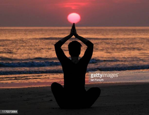 Jo Yaldren practices her yoga technique as the sun rises over Saltburn beach on August 25 2019 in Saltburn By The Sea England Temperatures are...