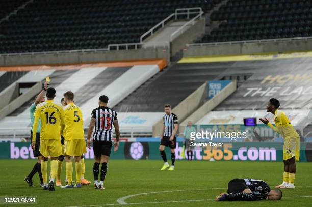 Joachim Andersen of Fulham FC receives a yellow card from Referee Graham Scott for a poor foul against Miguel Almirón of Newcastle United FC during...