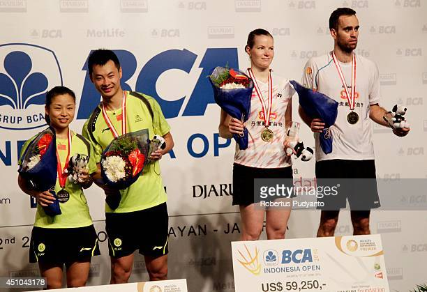 Joachim Fischer Nielsen and Christinna Pedersen of Denmark and Xu Chen and Ma Jin of China celebrate on the podium during the awarding ceremony BCA...