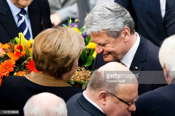 Joachim Gauck Lutheran pastor and former East German humanrights activist is congratulated by German Chancellor Angela Merkel of the Bundestag after...