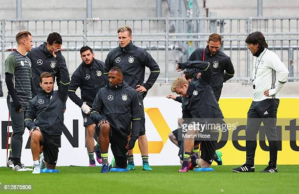 Joachim Loew coach of Germany talks with Mario Goetze and Jerome Boateng as they warm up during a training session at Millerntor Stadion on October 5...