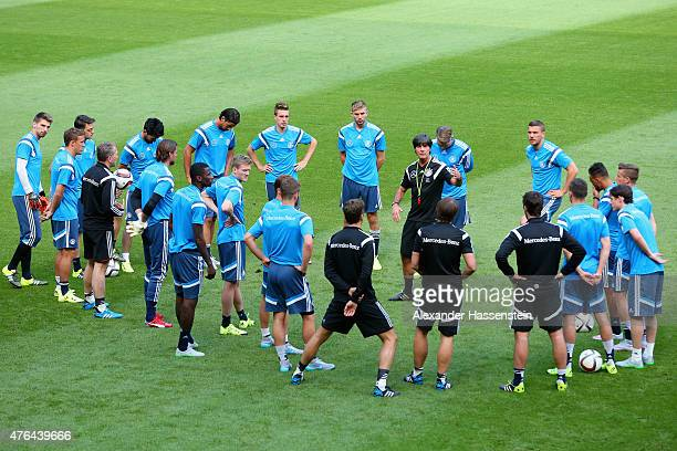 Joachim Loew head coach of German national team talks to his players prior to a training session at RheinErnergieStadion ahead of their international...