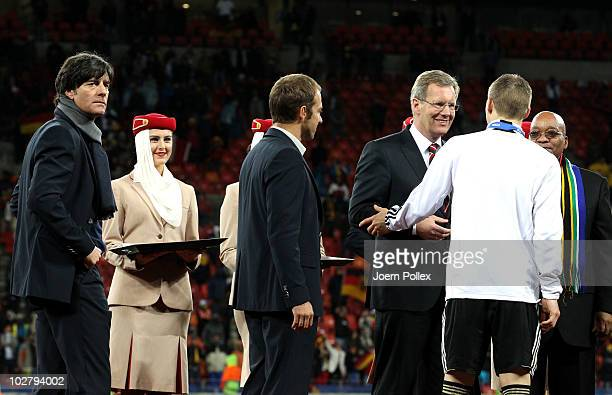 Joachim Loew head coach of Germany and assistant Hans Dieter Flick wait to receive their third place medals following the 2010 FIFA World Cup South...