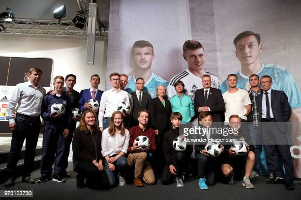 Joachim Loew head coach of Germany and Reinhard Grindel President of the Germany Football National Federation pose with kids from the German School...