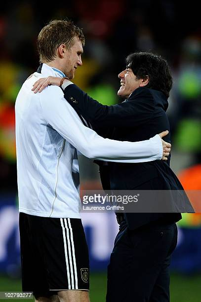 Joachim Loew head coach of Germany celebrates victory and third place with Per Mertesacker following the 2010 FIFA World Cup South Africa Third Place...