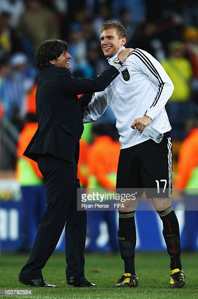Joachim Loew head coach of Germany celebrates victory with Per Mertesacker during the 2010 FIFA World Cup South Africa Third Place Playoff match...