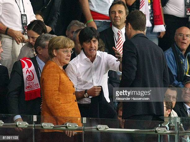 Joachim Loew head coach of Germany is seen on the tribune next to German chancellor Angela Merkel after been sent off due to an arguement with Josef...