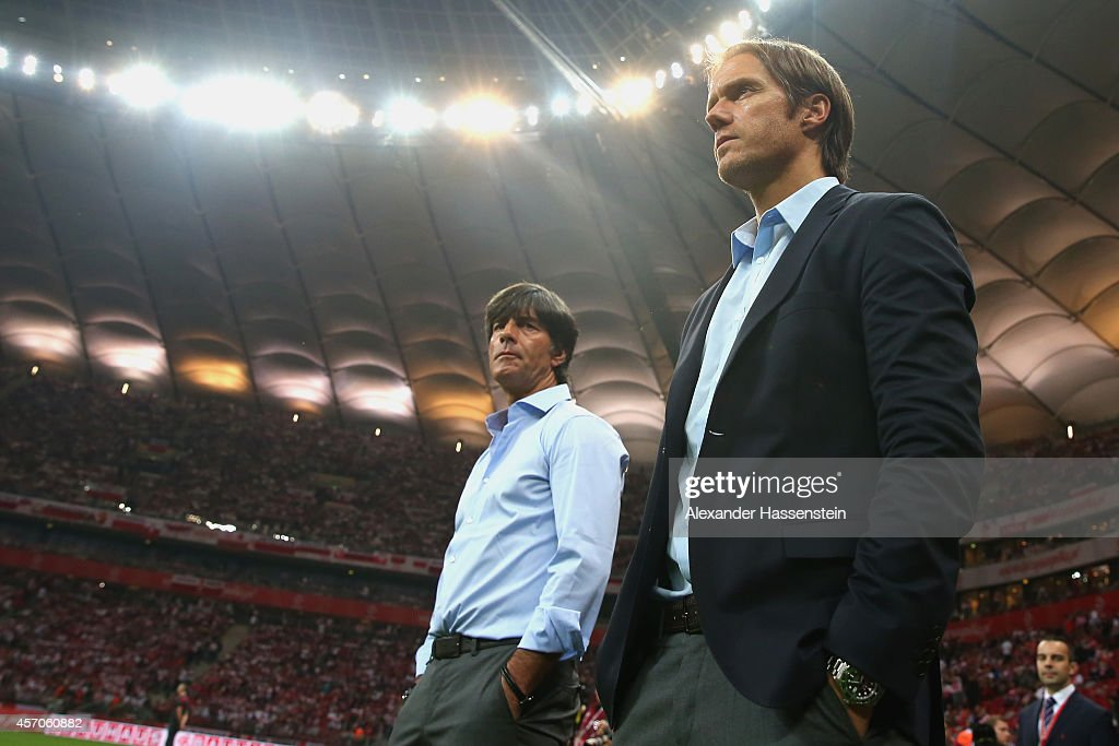 Joachim Loew, head coach of Germany looks on with his assistant coach Thomas Schneider (R) prior to the EURO 2016 Group D qualifying match between Poland and Germany at Narodowy Stadium on October 11, 2014 in Warsaw, Poland.