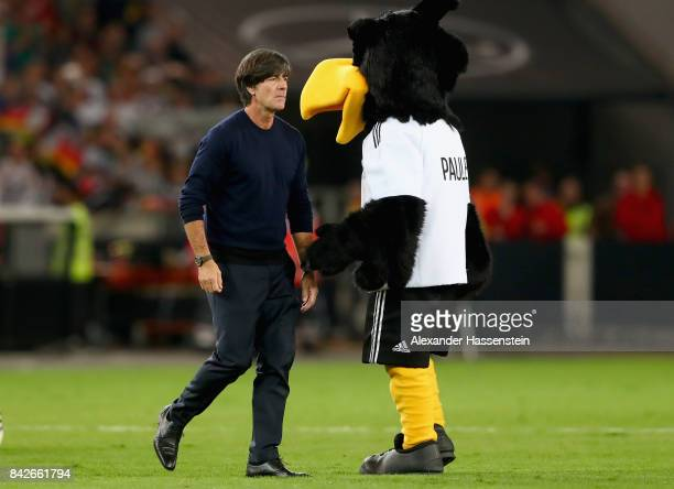 Joachim Loew head coach of Germany looks on with mascot Paule after to the FIFA 2018 World Cup Qualifier between Germany and Norway at MercedesBenz...