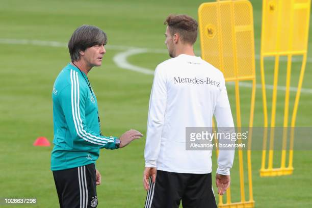 Joachim Loew head coach of Germany talks to his player Leon Goretzka during a Germany Training Session at Bayern Muenchen Campus on September 3 2018...