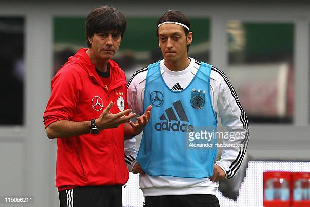 Joachim Loew head coach of Germany talks to his player Mesut Oezil during a training session ahead of their UEFA EURO 2012 qualifying match against...