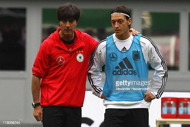 Joachim Loew , head coach of Germany talks to his player Mesut Oezil during a training session ahead of their UEFA EURO 2012 qualifying match against...