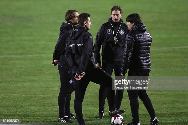 Joachim Loew head coach of Germany talks with his assistent coaches Marcus Sorg Miroslav Klose and Thomas Schneider during a training session of the...