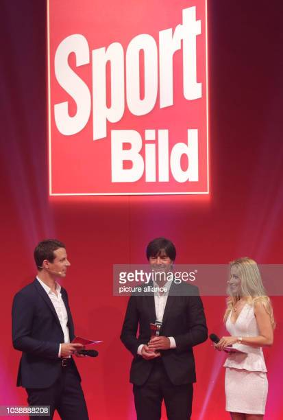 Joachim Loew head coach of Germany's national soccer team receives the 'Sonderpreis Chefredaktion' next to hosts Alexander Bommes and Andrea...
