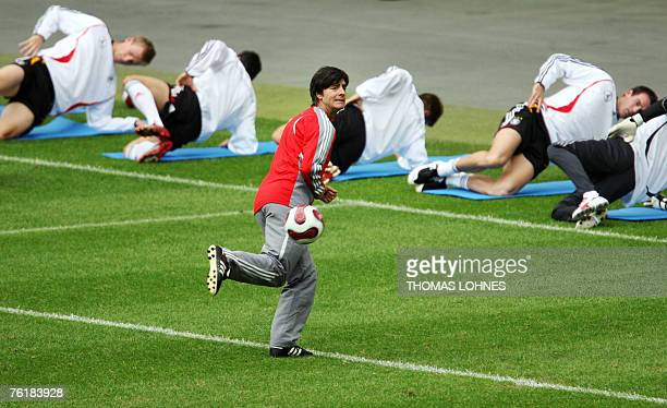 Joachim Loew head coach of the German national football team kicks the ball as his players stretch during a training session in Frankfurt/M western...