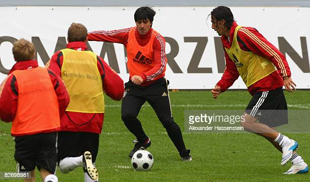 Joachim Loew head coach of the German National team challenges for the ball with Kevin Kuranyi and other players during a training session of the...