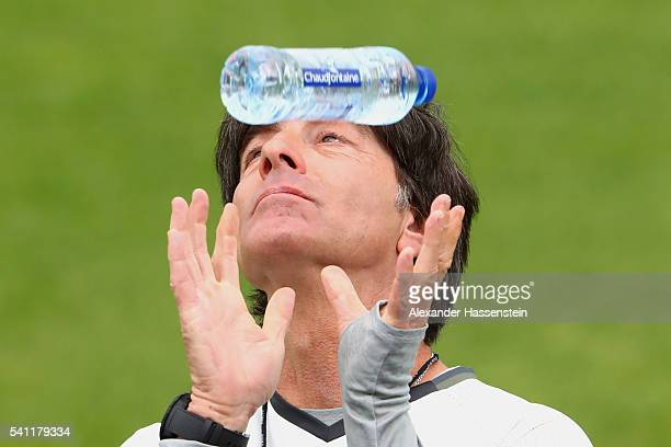 Joachim Loew head coach of the German national team plays with a mineral water bottle during a Germany training session at Ermitage Evian on June 19...