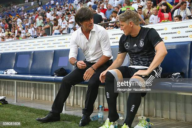 Joachim Loew head coach of the German national team talks to his player Bastian Schweinsteiger prior to the international friendly match between...