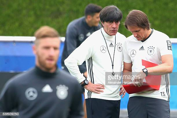 Joachim Loew head coach of the German national team talks to his assistant coach Thomas Schneider during a Germany training session ahead of the UEFA...