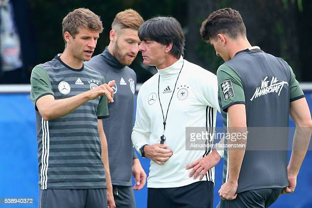 Joachim Loew, head coach of the German national team talks to his players Thomas Mueller , Shkodran Mustafi and Mario Gomez during a Germany training...