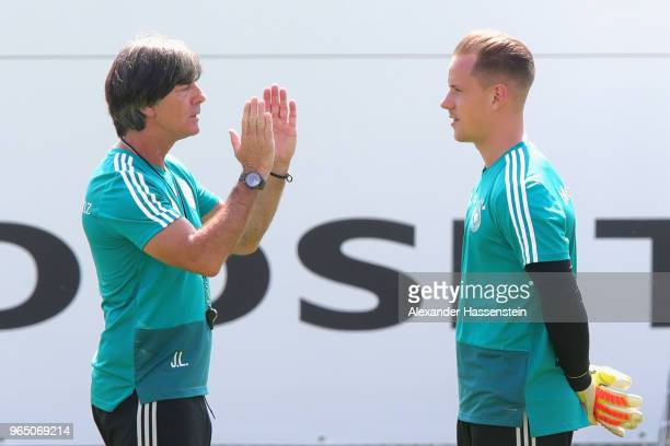 Joachim Loew head coach of the German national team talks to his keeper MarcAndre terStegen during a training session of the German national team at...