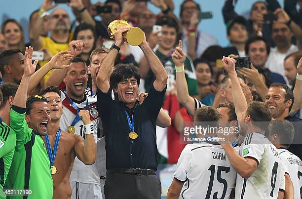 Joachim Loew of Germany lifts the World Cup trophy with his team after defeating Argentina 1-0 in extra time during the 2014 FIFA World Cup Brazil...