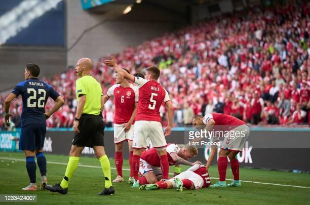 Joachim Maehle, Andreas Christensen, Simon Kjar, Martin Braithwaite helping Christian Eriksen of Denmark whos has collapsed on the pitch during the...