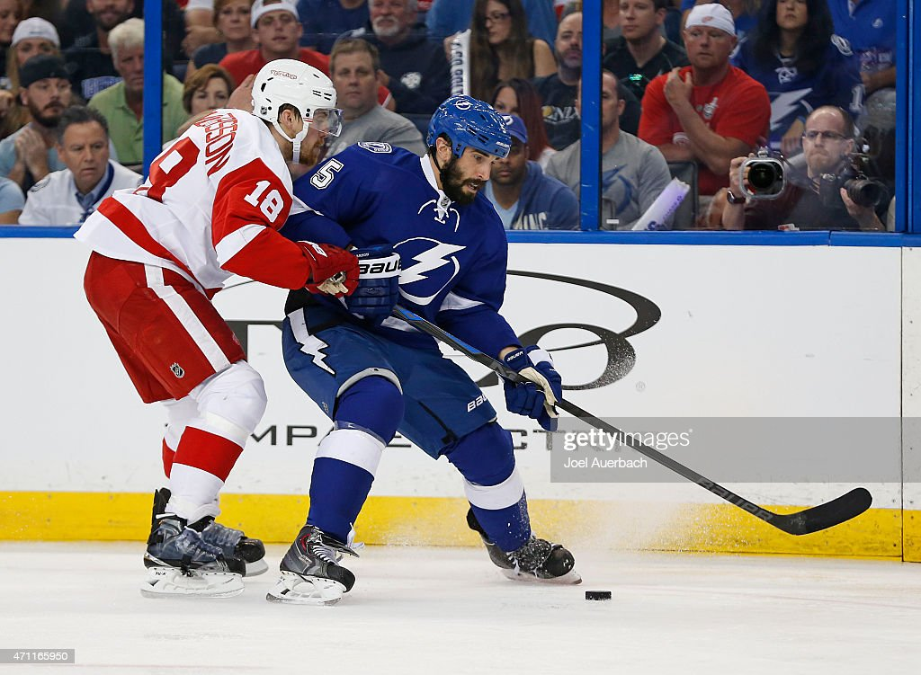 Joakim Andersson #18 of the Detroit Red Wings against and Jason Garrison #5 of the Tampa Bay Lightning battle for control of the puck along the boards during the first period in Game Five of the Eastern Conference Quarterfinals during the 2015 NHL Stanley Cup Playoffs at the Amalie Arena on April 25, 2015 in Tampa, Florida.