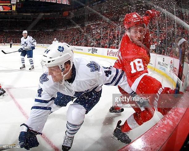 Joakim Andersson of the Detroit Red Wings and Morgan Rielly of the Toronto Maple Leafs battle in the corner during a NHL game on October 18 2014 at...