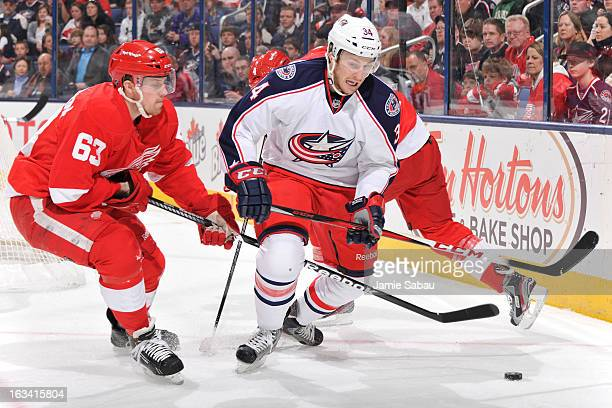 Joakim Andersson of the Detroit Red Wings and Nick Drazenovic of the Columbus Blue Jackets battle for possession of the puck during the first period...