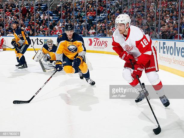 Joakim Andersson of the Detroit Red Wings carries the puck against Christian Ehrhoff of the Buffalo Sabres as Ryan Miller and Alexander Sulzer of...
