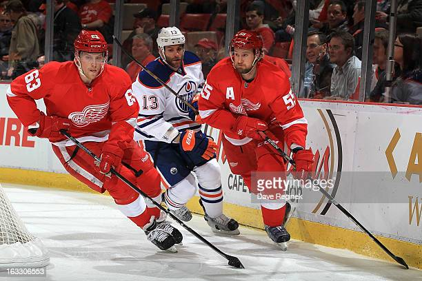 Joakim Andersson of the Detroit Red Wings skates with the puck as teamate Niklas Kronwall and Mike Brown of the Edmonton Oilers round the corner...