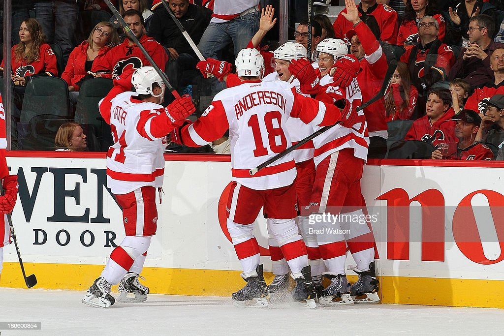 Joakim Andersson #18, Tomas Tatar #21 and teammates of the Detroit Red Wings celebrate a goal against the Calgary Flames at Scotiabank Saddledome on November 1, 2013 in Calgary, Alberta, Canada.
