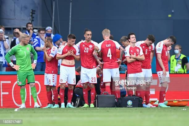 Joakim Maehle, Yussuf Poulsen, Simon Kjaer and Thomas Delaney of Denmark look dejected as team mate Christian Eriksen receives medical treatment...