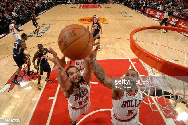 Joakim Noah and Carlos Boozer of the Chicago Bulls reach for a rebound during the NBA preseason game against the Indiana Pacers on December 20 2011...