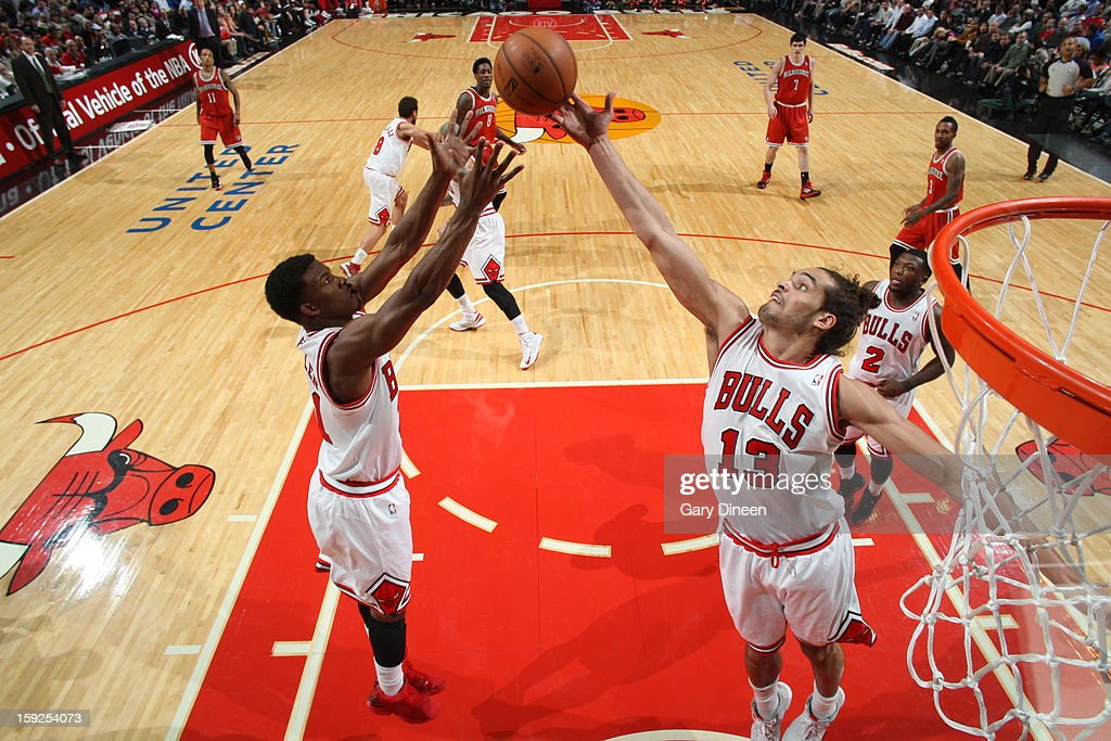 Joakim Noah #13 and Jimmy Butler #21 of the Chicago Bulls go up for a rebound against the Milwaukee Bucks on January 9, 2013 at the United Center in Chicago, Illinois.